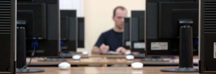 lokaal met computers en persoon achterin